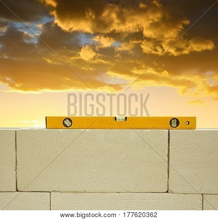 Spirit level on brick wall at sunset. Bricklaying work.