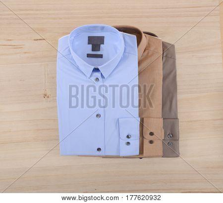 Three man shirt on wooden background