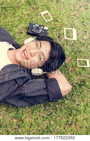 Asian guy lay down and listening music by headphones