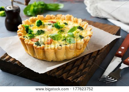 Homemade quiche tart with red fish salmon broccoli basil seasonings and cheese on a gray stone background. Selective focus.