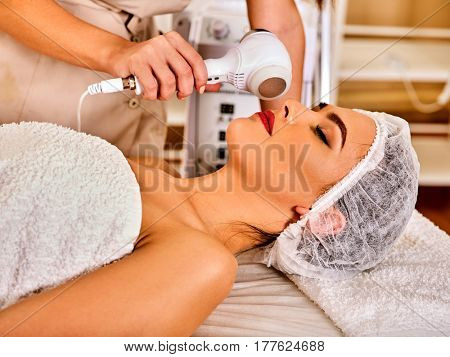 Ultrasonic facial treatment ultrasound face machine. Woman wearing medical hat receiving electric lift massage spa salon. Electronic stimulation female muscles. Skin care microcurrent therapy .