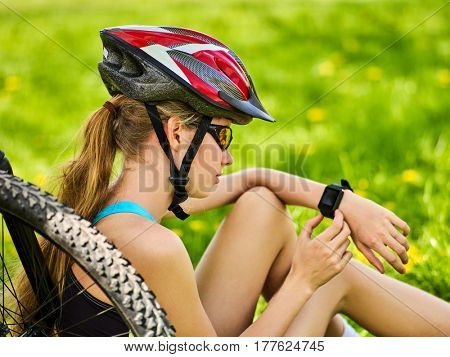 Woman traveling bicycle in summer park. Bicyclist girl watch on smart watch. Girl counts pulse after sport training. Cycling is good for health.