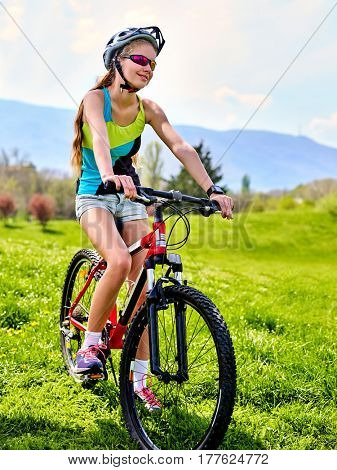 Woman traveling bicycle in summer park. Womens road bike for running on green grass. Cycling trip is good for health.