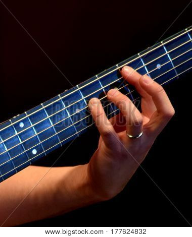 hand on the electrified five strings bass guitar