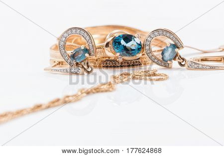 Gold Earrings In The Shape Of A Horseshoe And A Delicate Ring With Large Topaz
