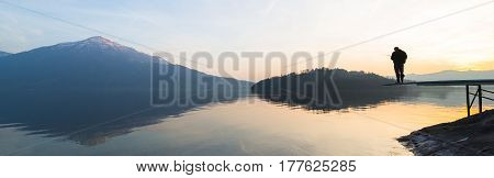 A man catches a fish. Happy relaxed hours alone with nature. Landscape of a mountain lake. Evening light of the setting sun. Male silhouette with a fishing rod in the backlight.