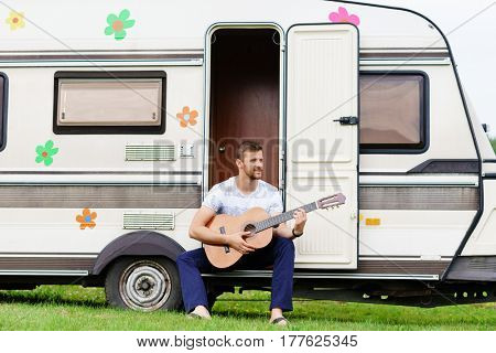 Young and handsome bearded guy playing guitar outdoors. Holiday, journey, vacation concept.