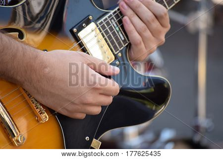 hand on the electric guitar with six strings