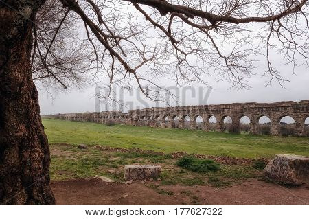 Ruins of an ancient Roman aqueduct made of tuff blocks. Photographed on a cloudy morning of spring.