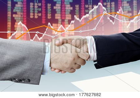Closeup of handshake on financial chart background