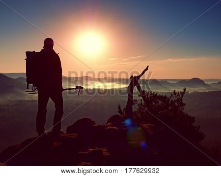 Tourist With Backpack And Poles Stand On Rock