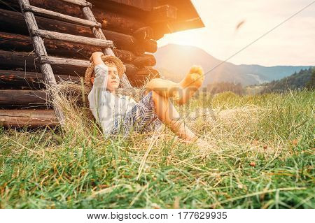 Boy sleeps in hay under the old barn