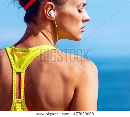 Young Fitness Woman Listening To Music At Embankment