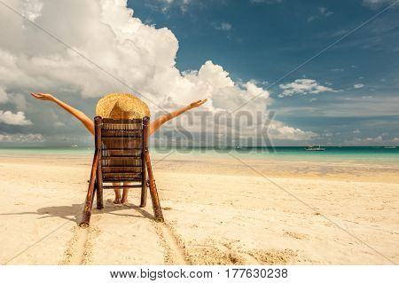 Woman on a tropical beach with hat, Boracay, Philippines.