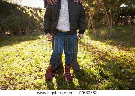Close Up Of Boy With Father Standing In Autumn Garden