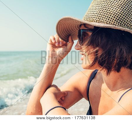 Woman in big hat enjoyes with sea view