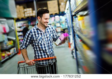 Man shopping in supermarket while pushing shopping cart