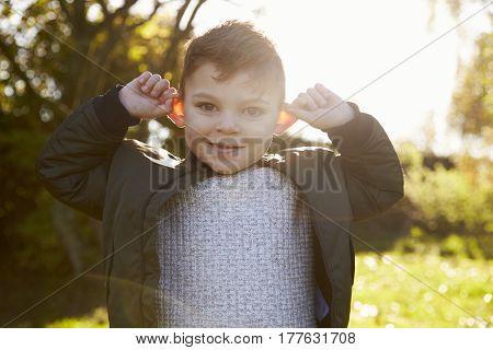 Portrait Of Boy Pulling Face In Autumn Garden