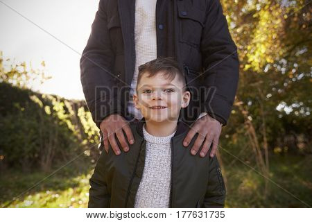 Portrait Of Boy With Father Standing In Autumn Garden