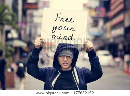 Asian guy holding placard free your mind motivation