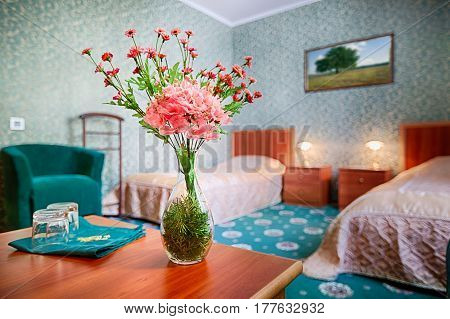 Hotel bedroom interior. Flower bouquet in suit with two single beds