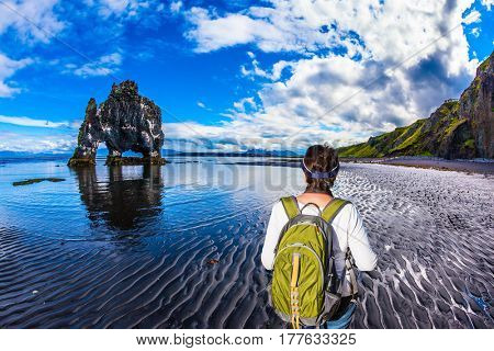 Woman with a green backpack admires magic Rock Hvitsercur. Northern coast of Iceland. Concept of extreme northern tourism