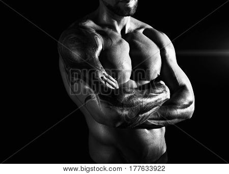 Athletic man's torso. Male fitness model show naked muscular body. Studio black and white shot, low key. Bodybuilding concept
