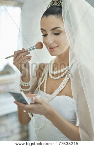 Young bride finishing makeup on wedding-day.