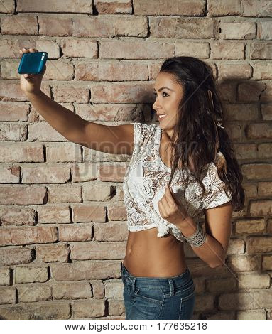 Pretty girl making selfie at summertime. Side view,