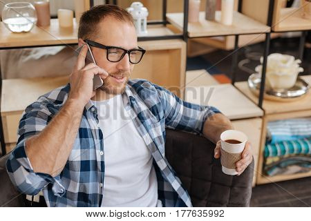 Speaking with people. Handsome bearded positive man holding a plastic cup and having coffee while speaking on the phone