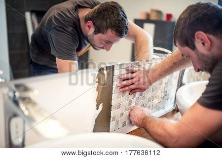 Close Up Of Handyman Fixing And Applying Ceramic Tiles On Bathroom Walls.