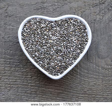 Chia seeds in a white heart shaped bowl on old wooden background.Salvia hispanica seeds.Healthy food or superfood concept.Selective focus.