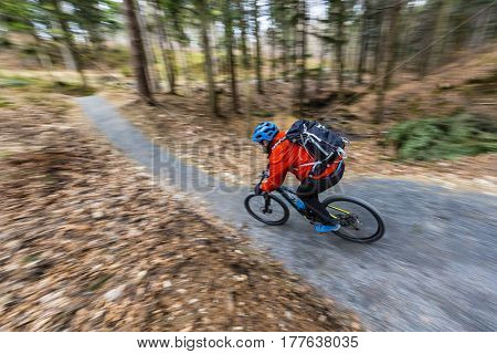 Mountain biker riding enduro on bike in early spring mountains forest landscape. Man cycling MTB enduro flow trail track. Outdoor sport activity.