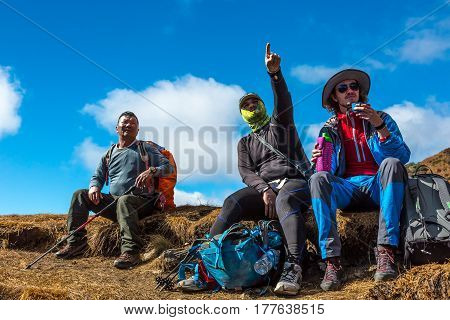 Group of active Travelers resting on Mountain Footpath pointing Hand forward