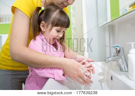 child girl and her mother washing hands with soap in bathroom