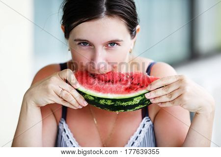 Pretty young woman eating a delicious sweet ripe watermelon. Shallow depth of field. Selective focus.
