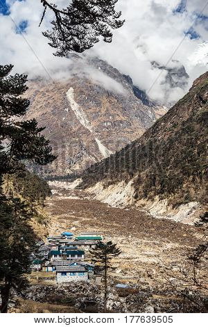 Small Village in remote Mountain Valley in Nepal Himalaya country. Pines on foreground and high Peaks slope covered by clouds on background