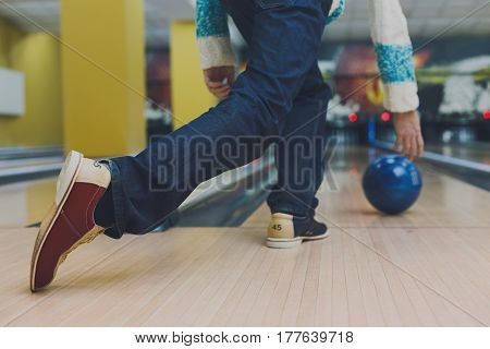 Unrecognizable man throw ball to bowling lane, closeup. Player plays active game, making strike. Cropped image of male leisure