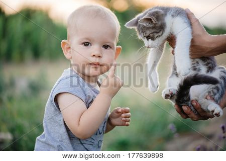 Portrait of a little girl with a cat, young child girl having fun with cat outdoor