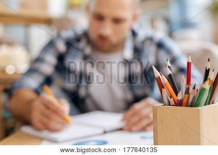 Tools for drawing. Selective focus of colored pencils standing in the wooden box with a nice pleasant handsome man drawing in the background