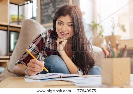 Talent and creativity. Beautiful joyful happy woman holding a pencil and smiling while drawing a picture in her notebook