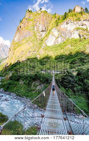 Woman backpacker crossing suspension bridge in Himalayas Nepal. Trekking and hiking with backpack in high mountains. Annapurna Himal Range on Annapurna Circuit Trek. Autumn season in Nepal Asia.