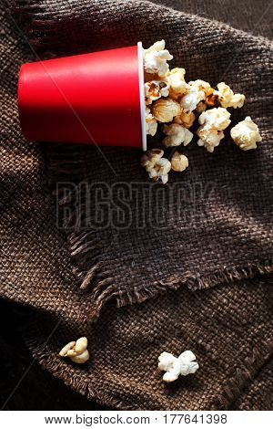 Fresh Popcorn in a red cardboard box on the wooden table Cinema concept