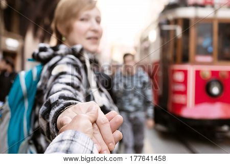 Follow me Concept Image smiling Woman in casual Jeans Shirt with small touristic Backpack holding Hand of Man and pulling toward Train