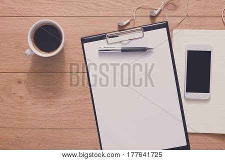 Writing, planning, naking checklist background. Study and work in office mockup. Top view of notepad, pen, coffee and mobile phone on wood with copy space
