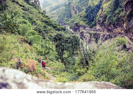 Female backpacker climbing with backpack in Himalayas Nepal. Trekking and hiking with backpack in high mountains. Annapurna Himal Range on Annapurna Circuit Trek. Autumn season in Nepal Asia.