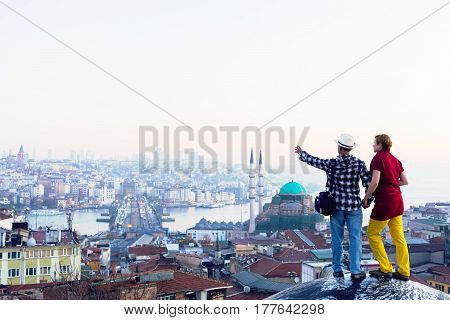 Man and Woman in casual travel Clothing on roof of Building at eastern city with copy space