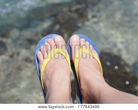 Selfie bare feet wearing colorful sandal over sea water background