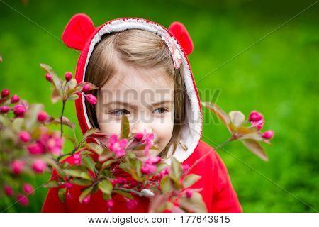 Girl sniffs a flower. Spring botanical garden