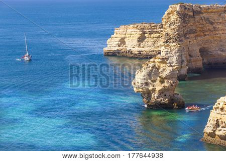 Boats with tourists visiting the caves at Marinha beach, Algarve Portugal